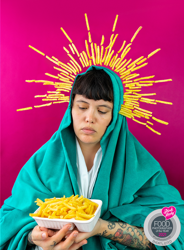 A photo showing Dorothy Porker posed as the virgin Mary but cradling a tray of fries instead, covered in a bright turquoise head dress with white trim at the neck and hands in front of a pinkish background, a crown of fries floats around her head and there is a logo for the Pink Lady Food Photographers of the Year 2021 Shortlist in the righthand bottom corner.