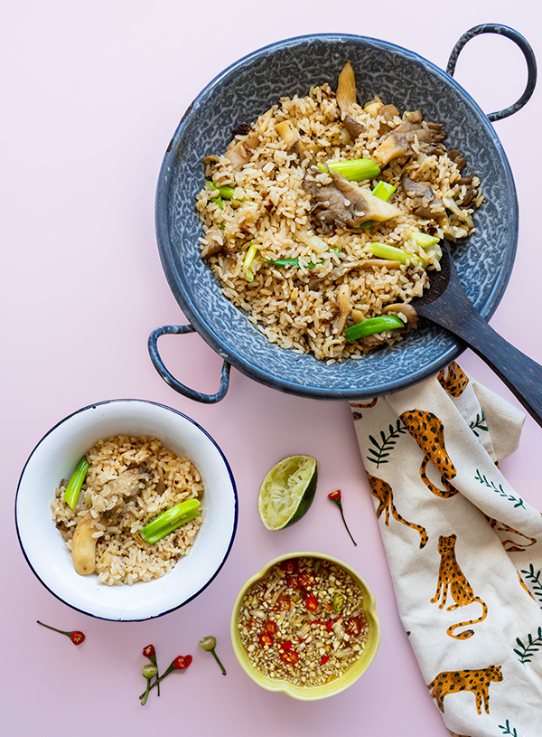 An overhead shot on a soft pink background. At the top of the image is a small blue 'cloudy' enamel wok filled with Thai fried rice showing bits of oyster mushrooms and spring onions, there is a wooden rice ladle stuck in the pot. The wok is set on a dish towel with a leopard print. To left bottom of the wok there is a small enamel white bowl with a white trim filled with more Thai fried rice. Scattered around it are the tips of birds eye chilies as well as a squeezed half of lime. Finally at the middle bottom of the image there is a yellow bowl filled with nam pla prik, a Thai dipping sauce which has garlic and thin slivers of birds eye chilies floating in it.