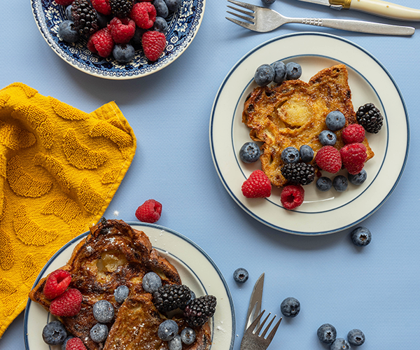 An overhead shot of a blue backdrop, there are two white plates with a blue trim, both have stollen French toast and a mixture of red fruits on top. There is a bowl of more red fruit and two sets of knives and forks with the plates. There are two yellow towels with croissant prints flanking the plates at the top and bottom and some more red fruits scattered around the bottom plate.