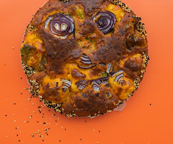 An overhead shot of a round broccoli and cauliflower cake on a bright orange background, a face has been made out of circles of onion on top of the cake, though it's been distorted in the baking process, there are nigella and sesame seeds sprinkled around the cake.