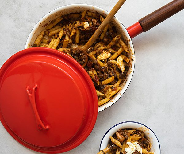 A large red pan with a dark wooden handle is filled with rigatoni pasta with red sauce and bits of mozzarella, there is a wooden spoon poking outside of the pan and there is a red lid half covering it. There is a small white bowl with blue rim filled with more pasta off to the bottom of the photo, with a bamboo handle sticking out of it. All are placed on a cement backdrop.