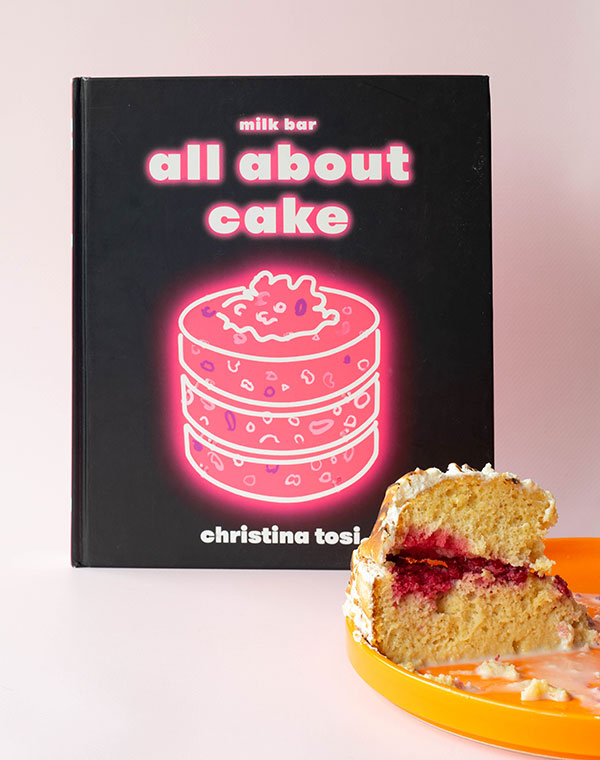 The cookbook All About Cake by Christina Tosi with an orange plate with a wedge of pastel tres leches in front of it.