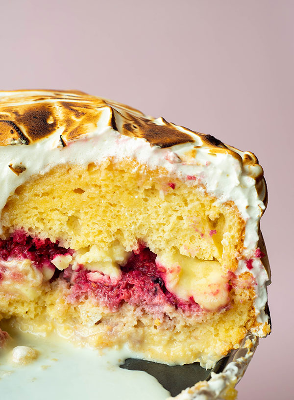 A close up of a slice of tres leches cake with layers of milk-soaked cake, raspberries and milk crumbs, more milk soaked cake and a covering of toasted meringue.