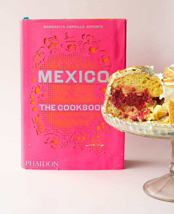 The cookbook Mexico The Cookbook by Margarita Carrillo Arronte with pieces of pastel tres leches on a cake stand off to the side of the image.