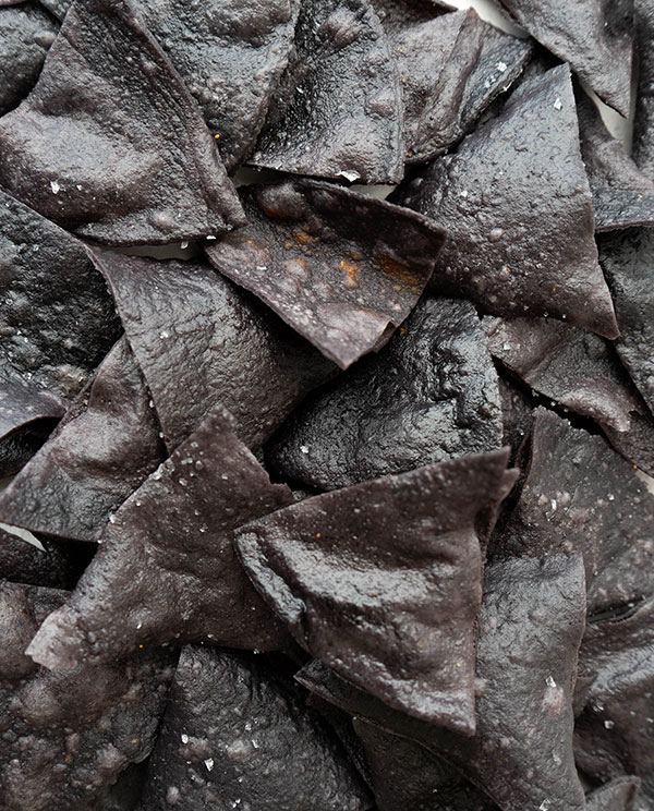 A closeup of salted black totopos (fresh fried nachos made from fresh tortillas).