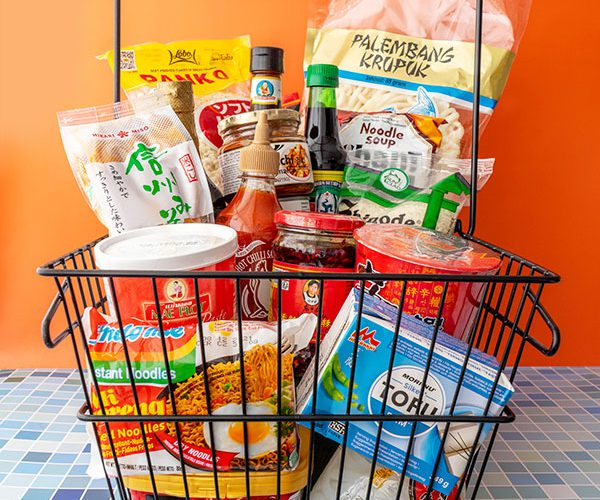 A grocery basket filled with Asian ingredients, supplies, snacks and ready-meals.