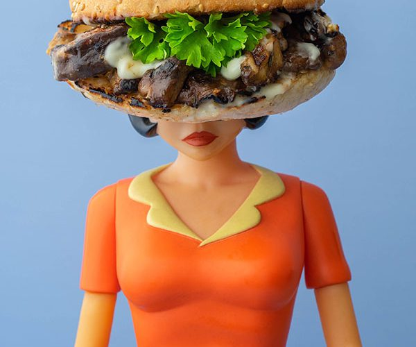 A doll who's face is covered by a jerk mushroom bun with mayonaise and parsley.