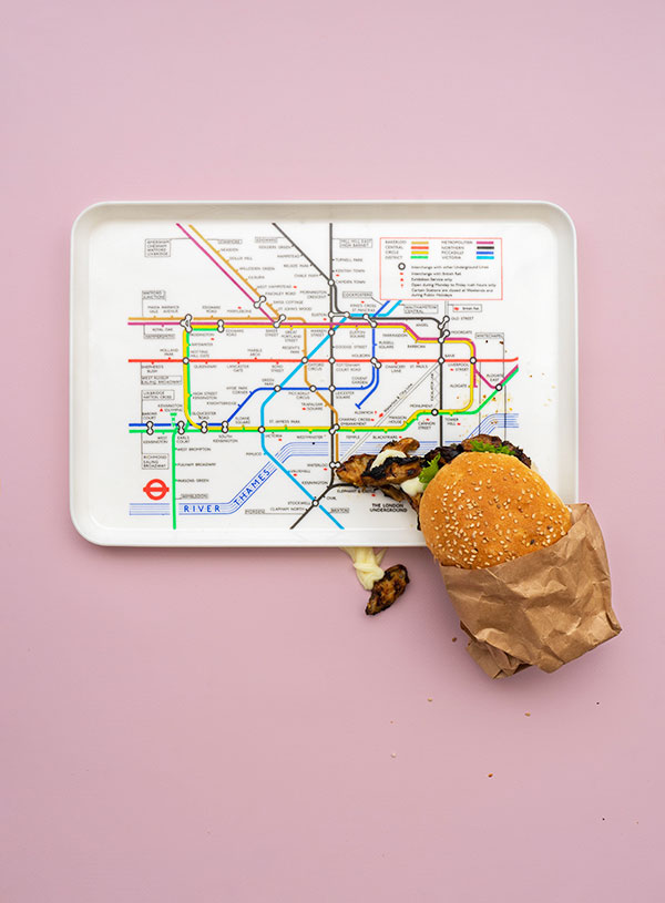 A server tray with the London tube map on it and a paper wrapper jerk bun perched on the bottom right side of it with mushrooms and mayonaise spilling out around it.