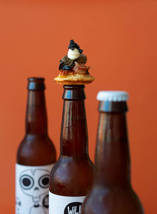 Three bottles of WillsArk beer, one of which is topped with a silver dollar kimchi pancake, topped with kimchi, a smoked oyster, Kewpie mayo and imitation caviar.